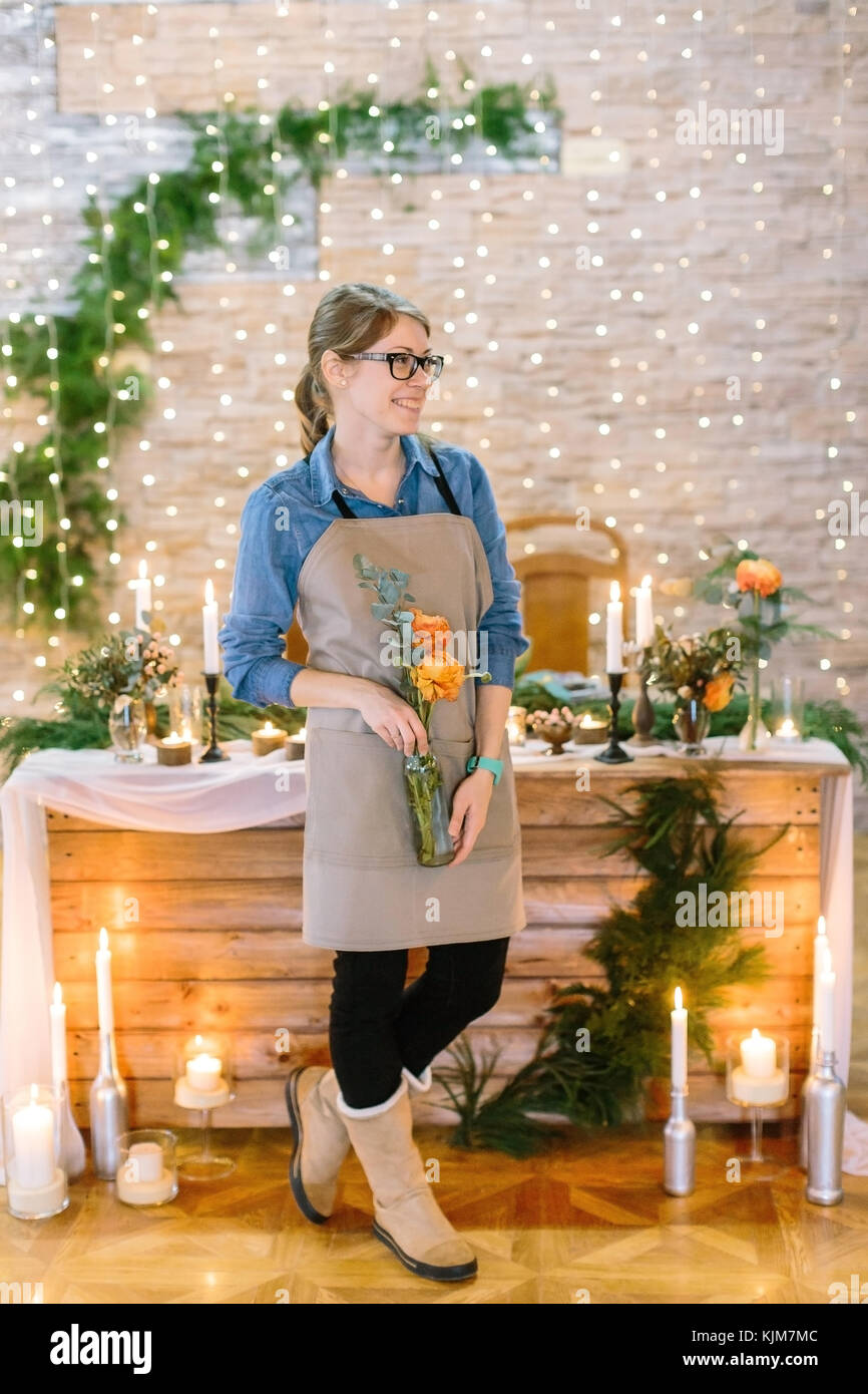 floral design, profession, decoration concept. cute smiling girl dressed in clean apron and comfortable shirt holding - Stock Image