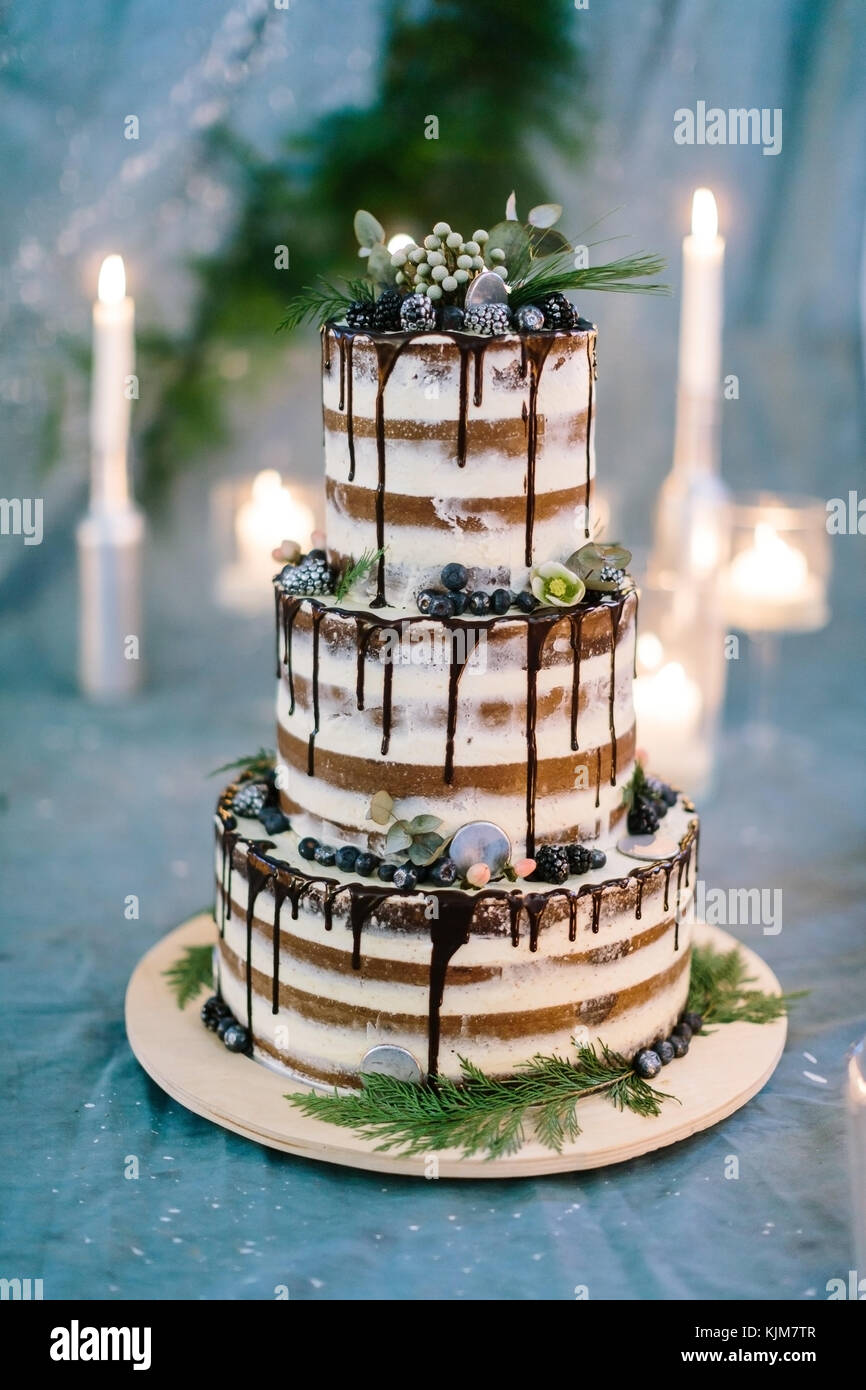 cooking, sweetness, wedding concept. close up of three tier amazing cake with white and brown streeps and chocolate - Stock Image