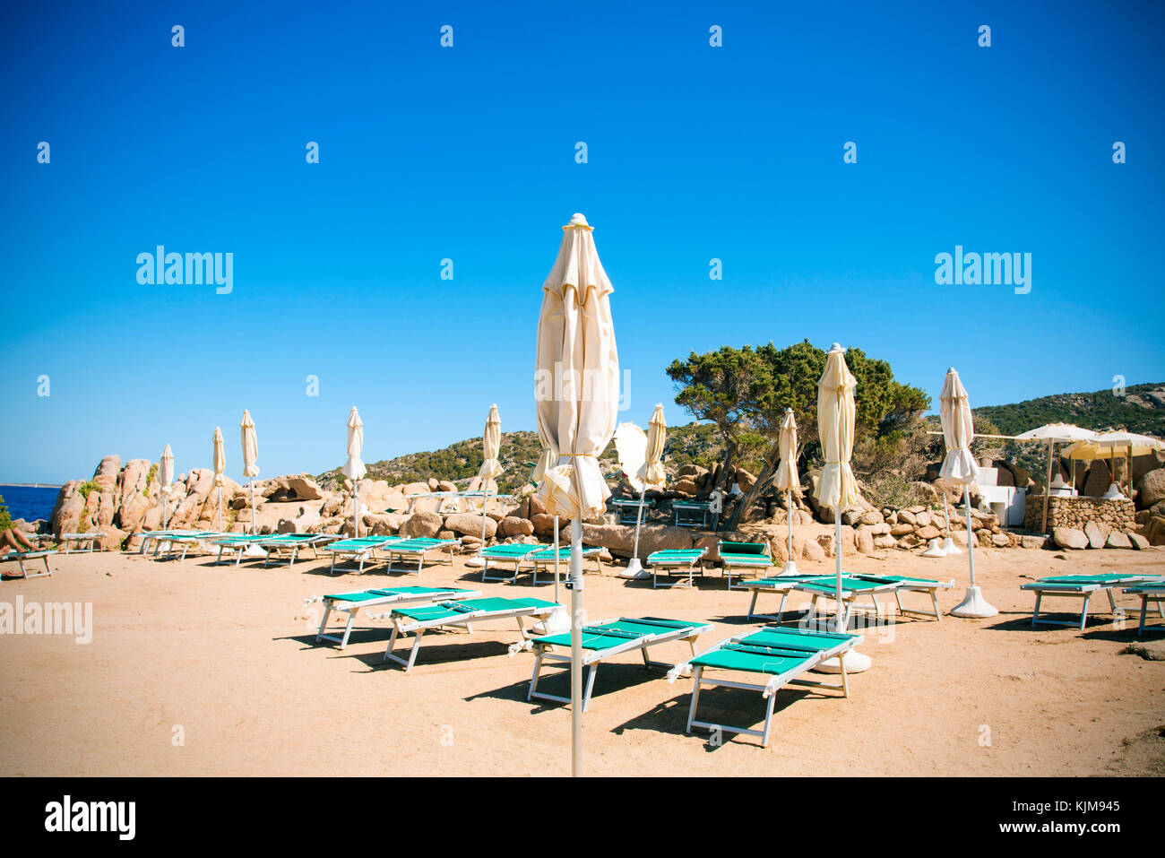 some sunloungers and umbrellas in a beach in Baja Sardinia, Sardinia, Italy - Stock Image
