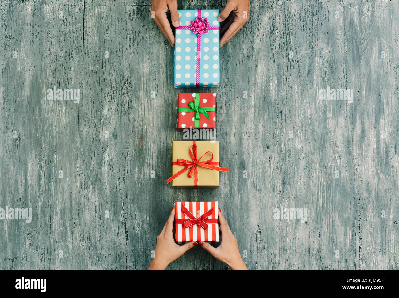 high-angle shot of a young caucasian woman and a young caucasian man exchanging gifts on a gray rustic wooden table, - Stock Image