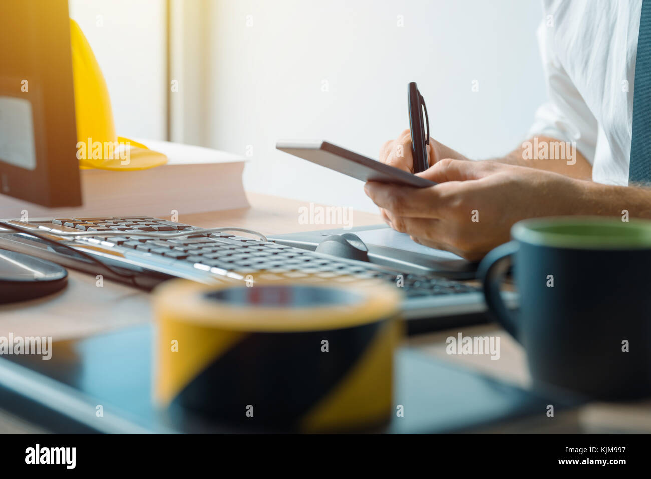 Civil engineer using smartphone in office during the construction industry project development - Stock Image