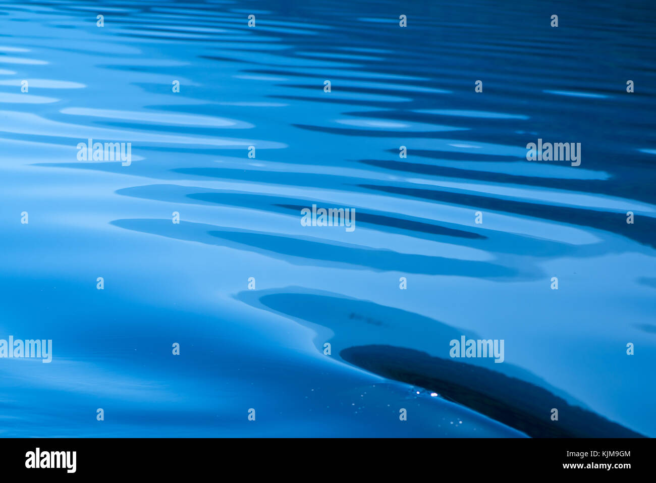 Blue rippled water as abstract background. Tranquil surface texture of the lake. - Stock Image