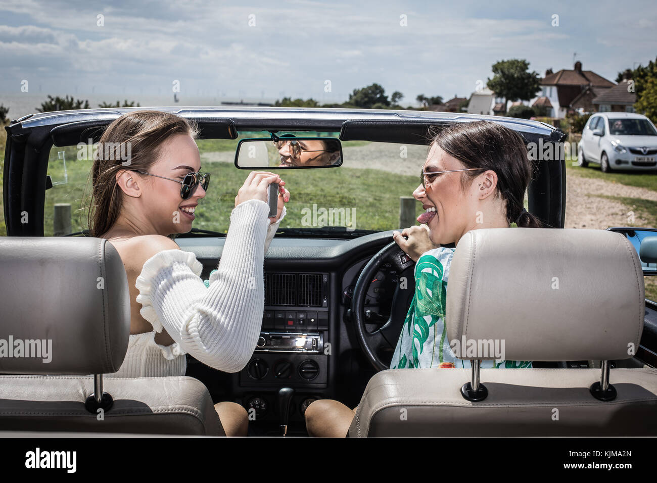 Two beautiful young women on a summer road trip together in a convertible car. - Stock Image