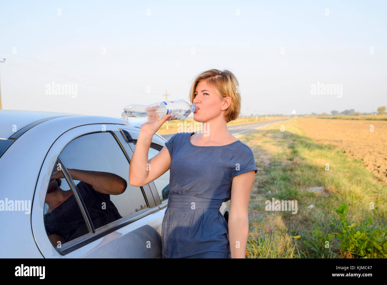 Slavyansk-on-Kuban, Russia - September 17, 2017: The girl quenches his thirst. Blonde drinks water from a plastic - Stock Image