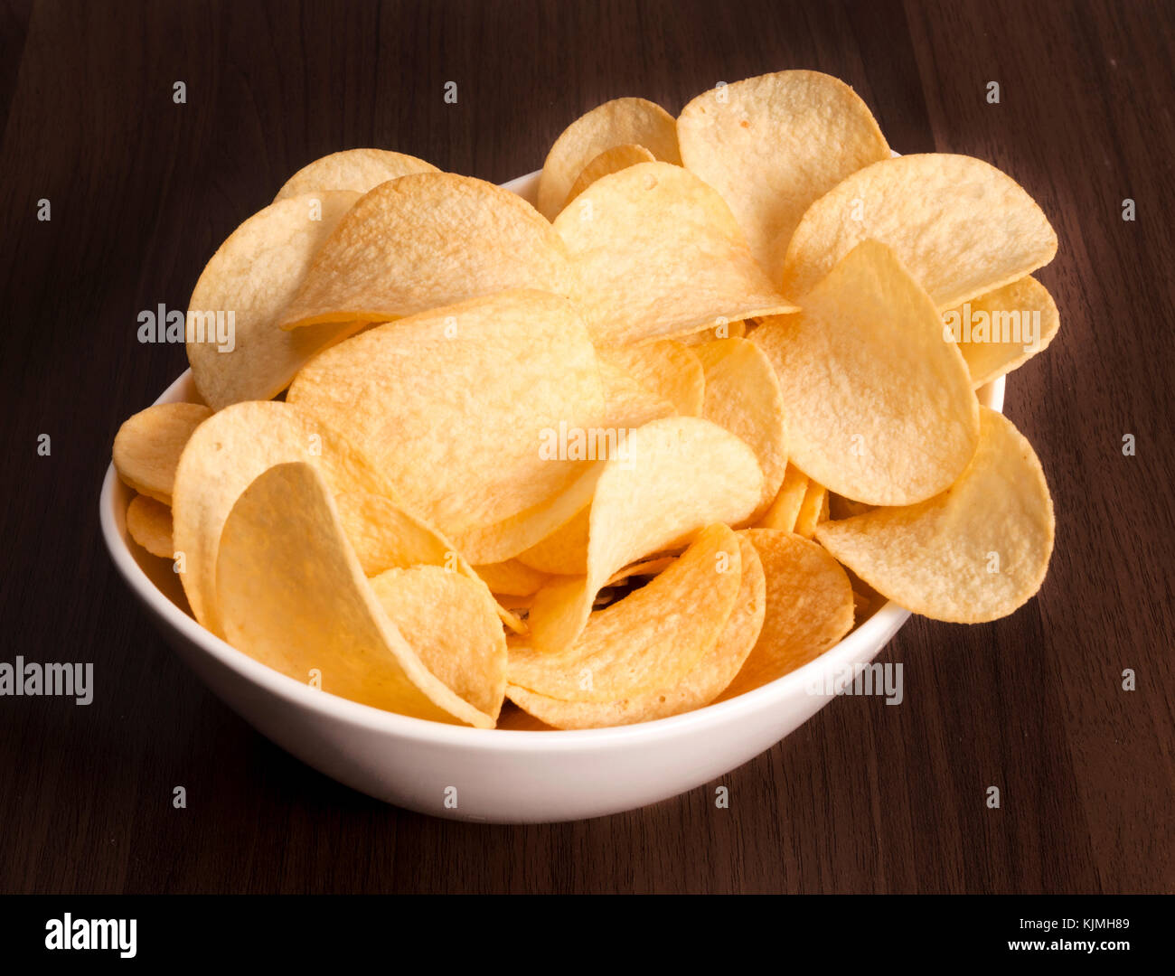 Cup of potato chips on the wooden background in low key - Stock Image