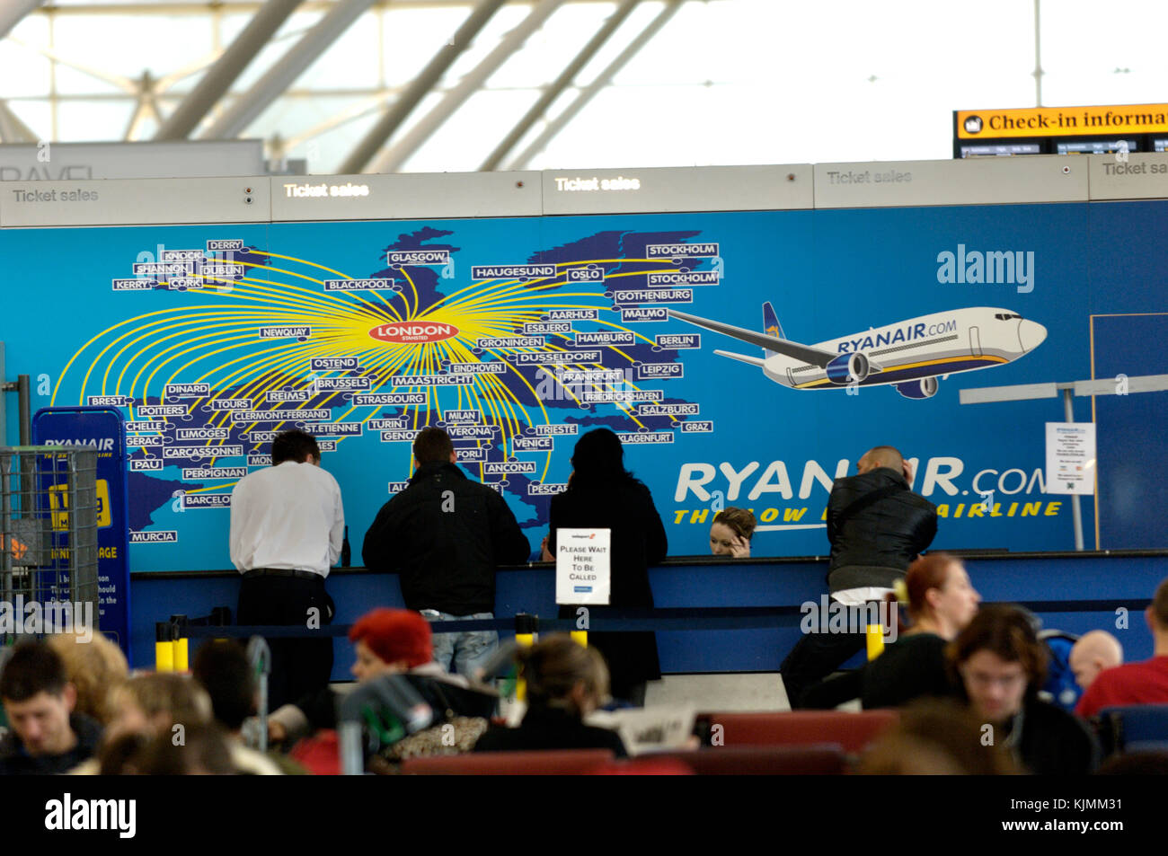 passengers at the ticket sales & excess baggage payments desk with a route map on the wall behind, others sitting - Stock Image