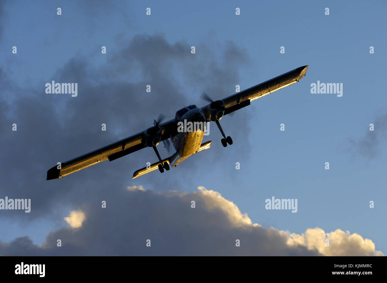 sun glinting off the fuselage and wings with dark clouds behind - Stock Image