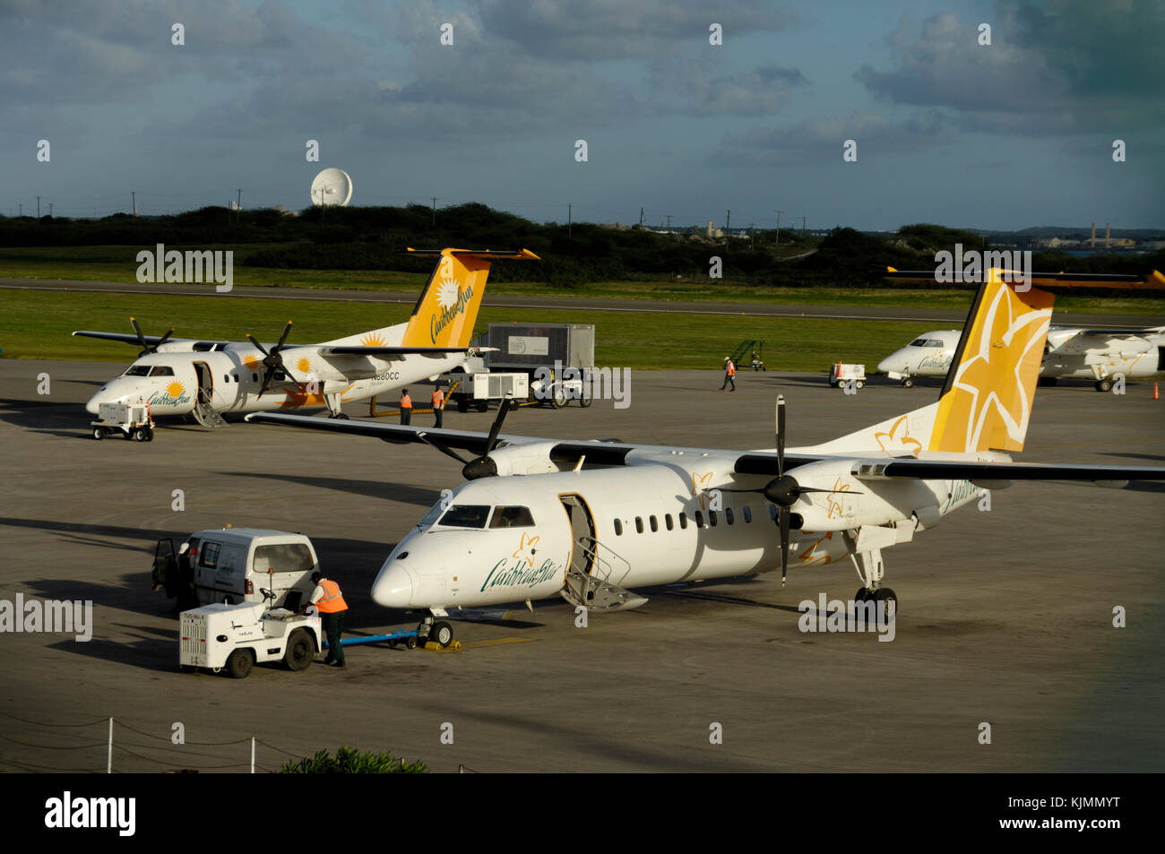 Men wearing yellow high-viz tabards walking to a tug with a towbar, Caribbean Star Airlines Bombardier DHC-8 with - Stock Image