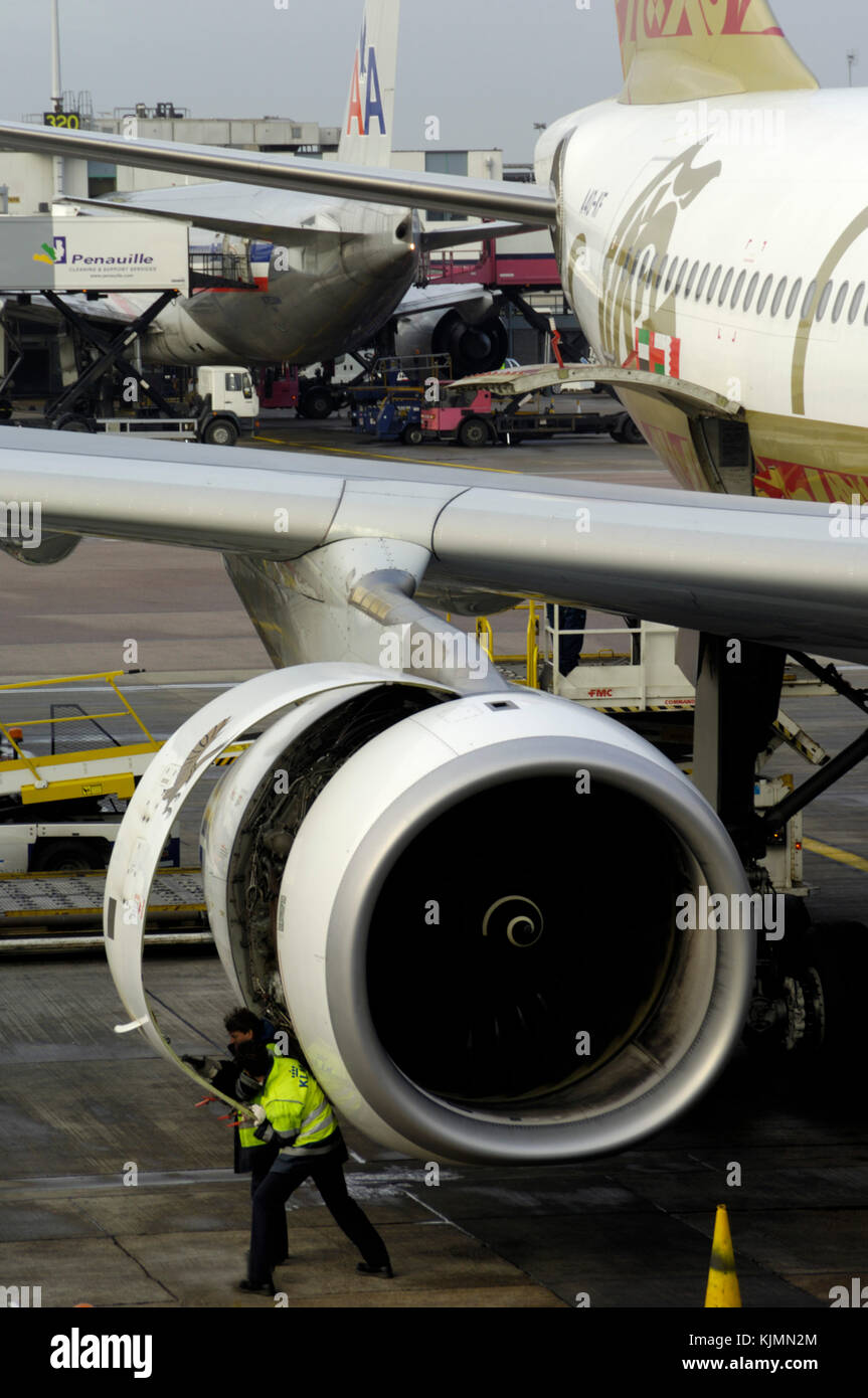 a Rolls-Royce Trent 772B-60 engine on a Gulf Air Airbus A330-200 being inspected by men wearing yellow high-viz Stock Photo