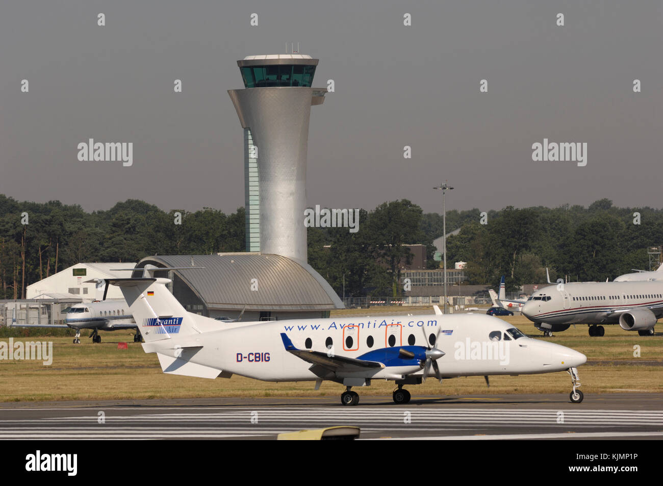 Avanti Air Beechcraft 1900D taxiing, Boeing 737-700 BBJ and Gulfstream 500 parked and the air-traffic control-tower - Stock Image