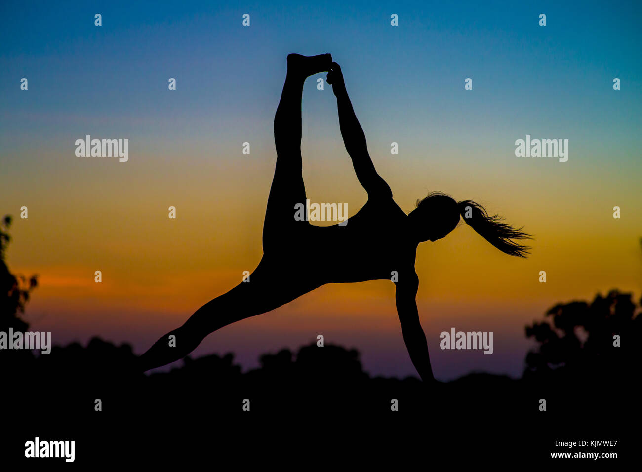 Woman doing yoga as a silhouette in front of a sunset. - Stock Image