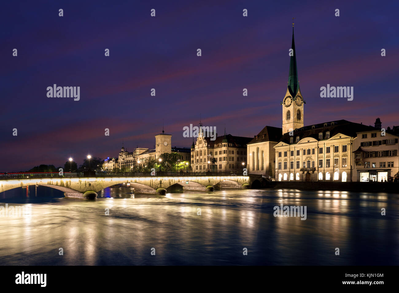 View of historic Zurich city center with famous Fraumunster Church and river Limmat at Lake Zurich , in twilight, - Stock Image