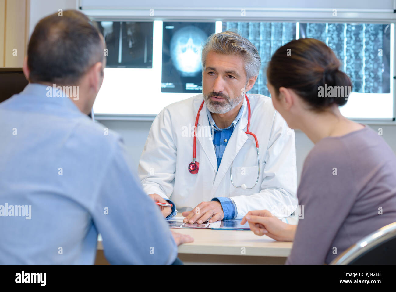 Doctor talking seriously to middle aged couple Stock Photo