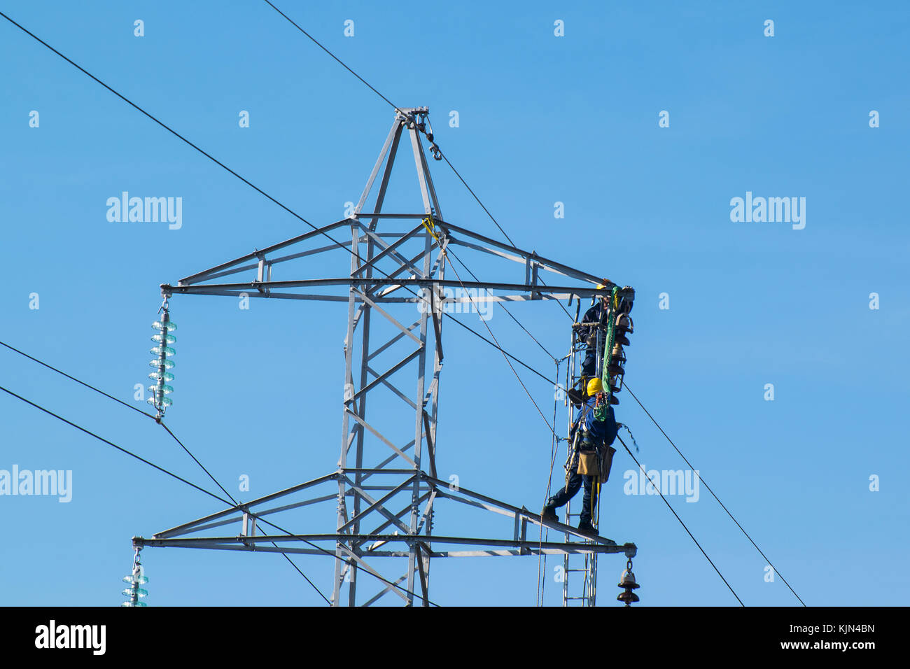 Construction workers fixing above ground electricity wires - Stock Image