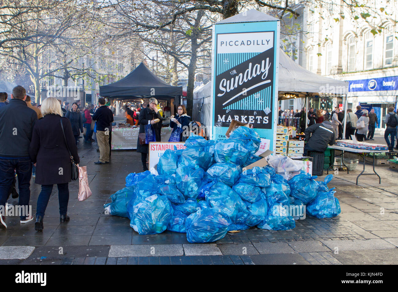 A pile of decaying bin bags and food waste rubbish next to Manchester Christmas market stalls Stock Photo