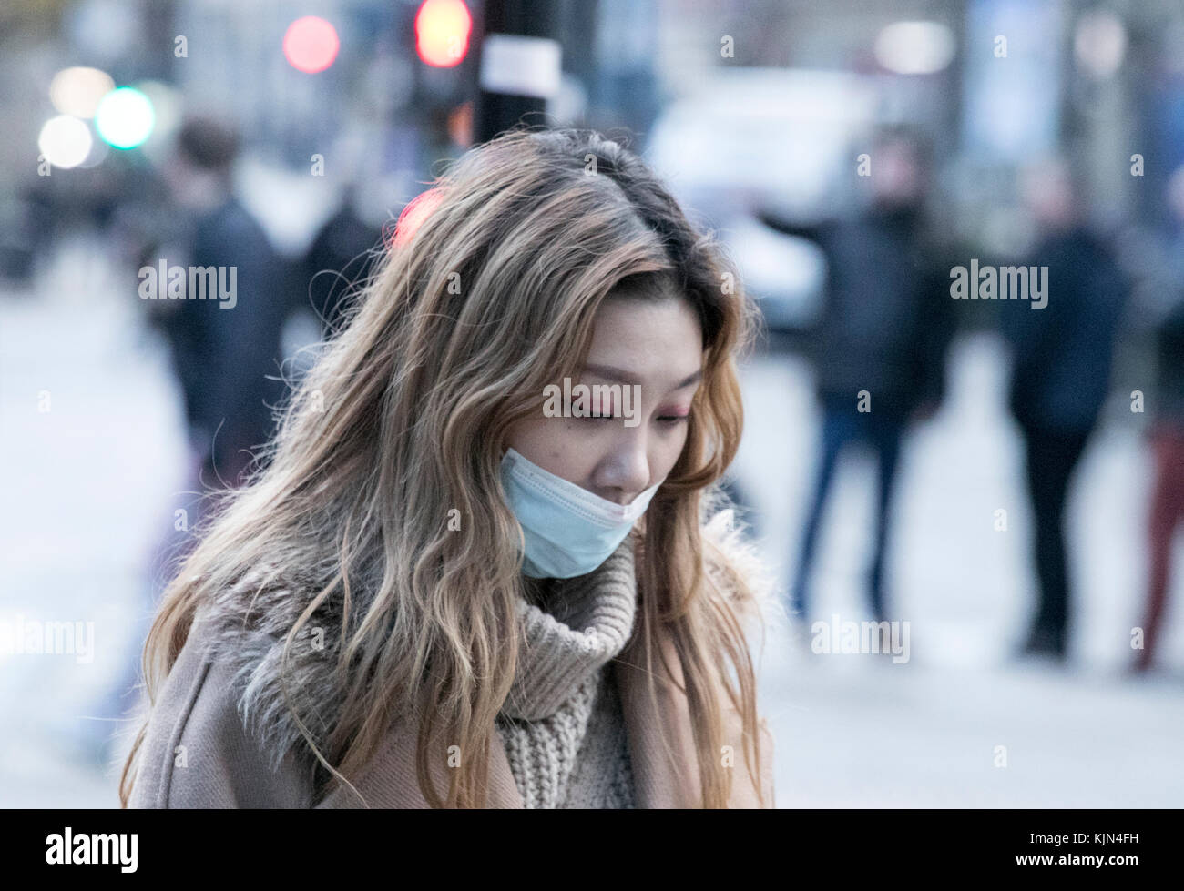 An Asian or Oriental girl wears a pollution face mask as she walks the city streets of Manchester, England, United - Stock Image