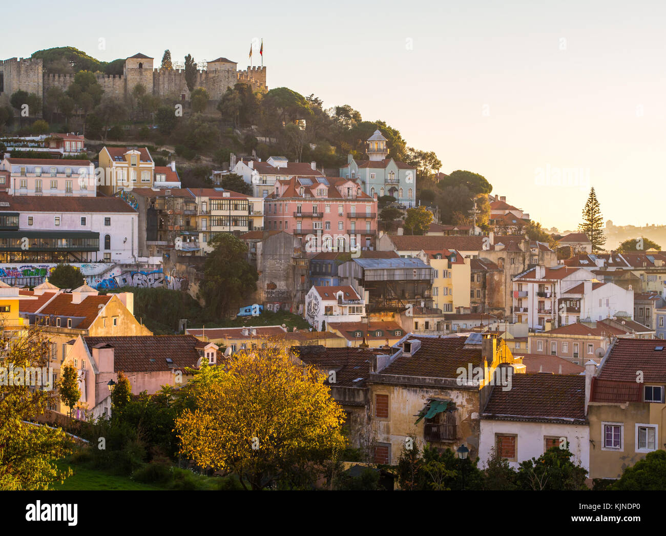 Soa Jorge Castle in Lisbon, Portugal, with the sourrounding architecture, at sunset. - Stock Image