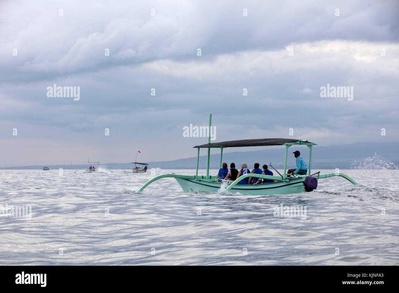 Local fishermen in traditional outriggers with tourists during dolphin watching tour at Lovina Beach, Buleleng Regency - Stock Image
