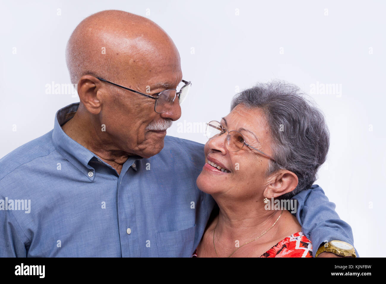 An smiling elderly couple, both wearing glasses. - Stock Image