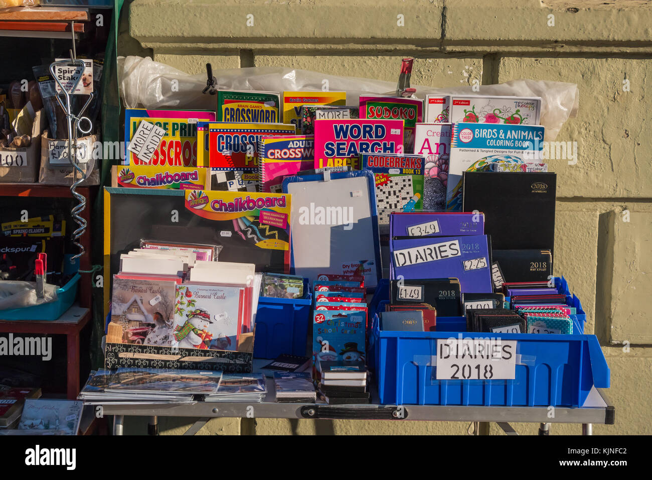 A colourful display of 2018 diaries, puzzle books, calendars and other stationery in bright winter sunshine - Stock Image