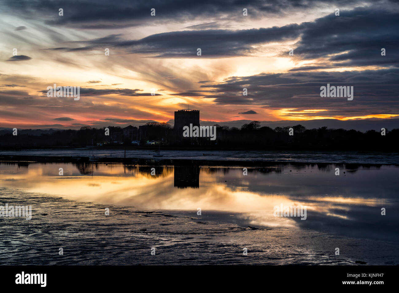 sillouette of Portchester castle at dusk with sunset, low tide. - Stock Image