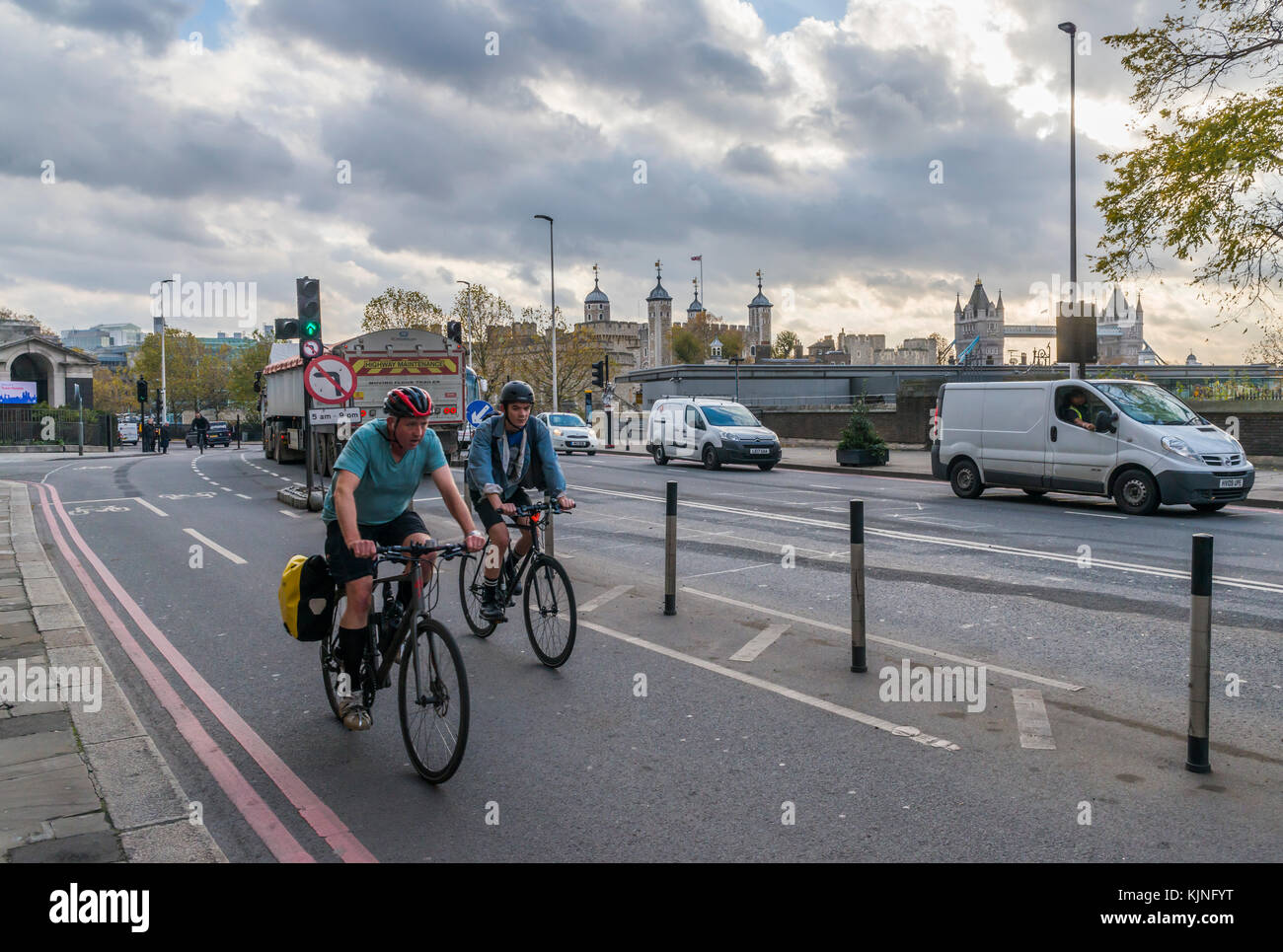 two cyclists on segregated cycling lane near Tower Hill in the City of London, UK - Stock Image