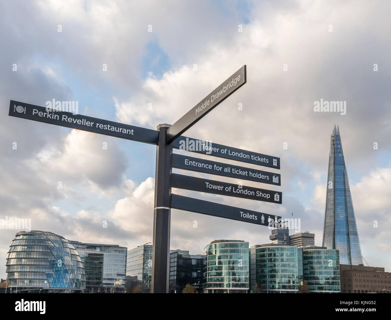Sign posts with major attractions near Tower HIll in London with modern buildings background, including the Shard - Stock Image