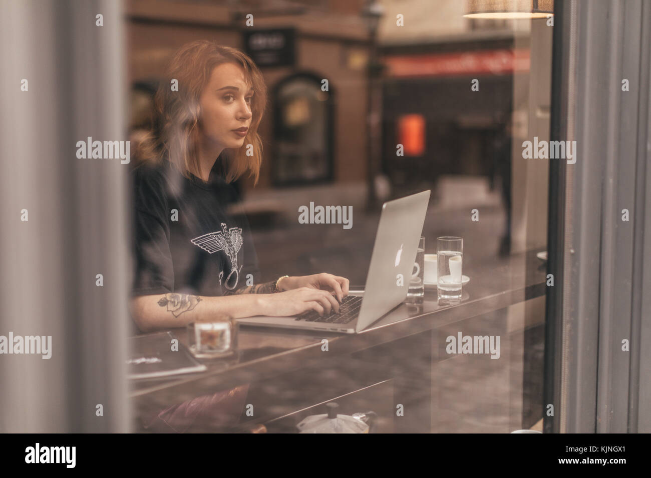 Pretty girl drinking coffee and working on her lap top in a bar - Stock Image
