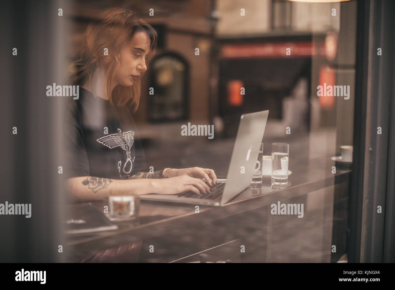 Pretty girl working on her lap top in a bar - Stock Image