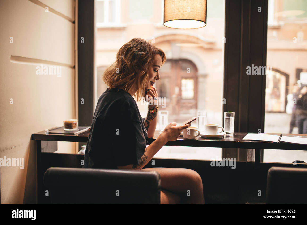 Cute girl texting on her cell phone in a bar - Stock Image