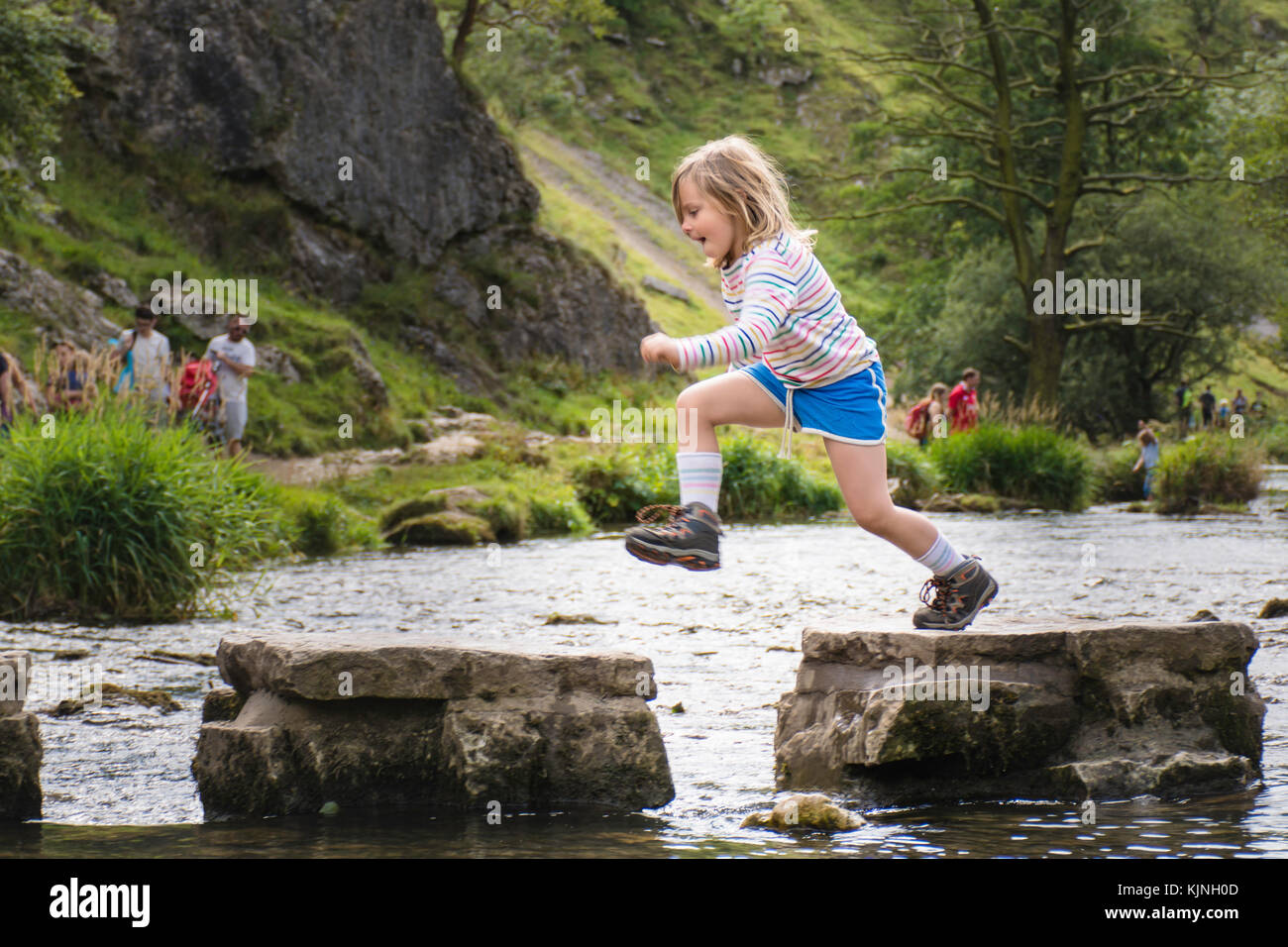 girl leaping over the stopping stones at Dovedale, derbyshire - Stock Image