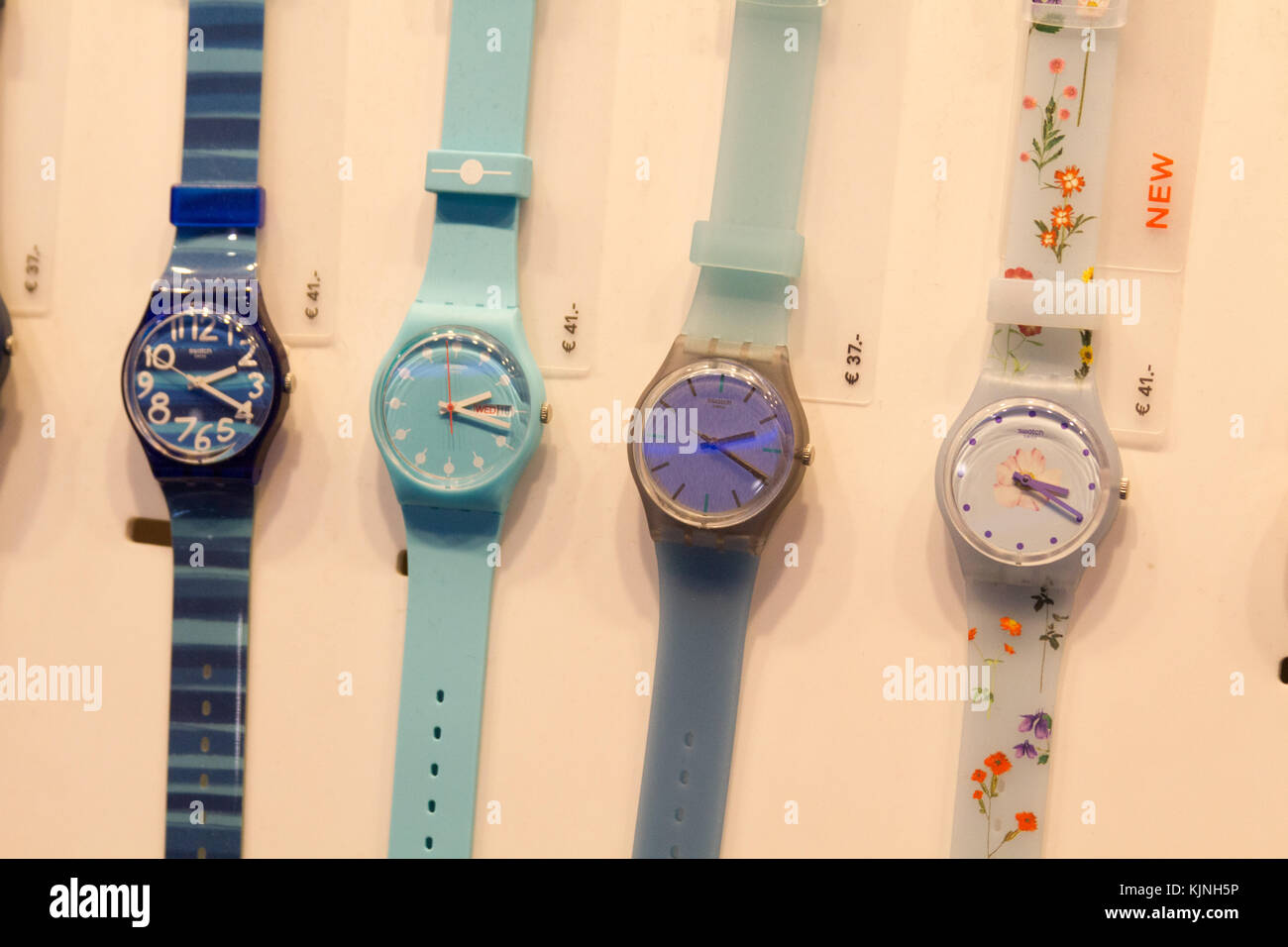 Swatch wristwatches arrayed in a shop. - Stock Image