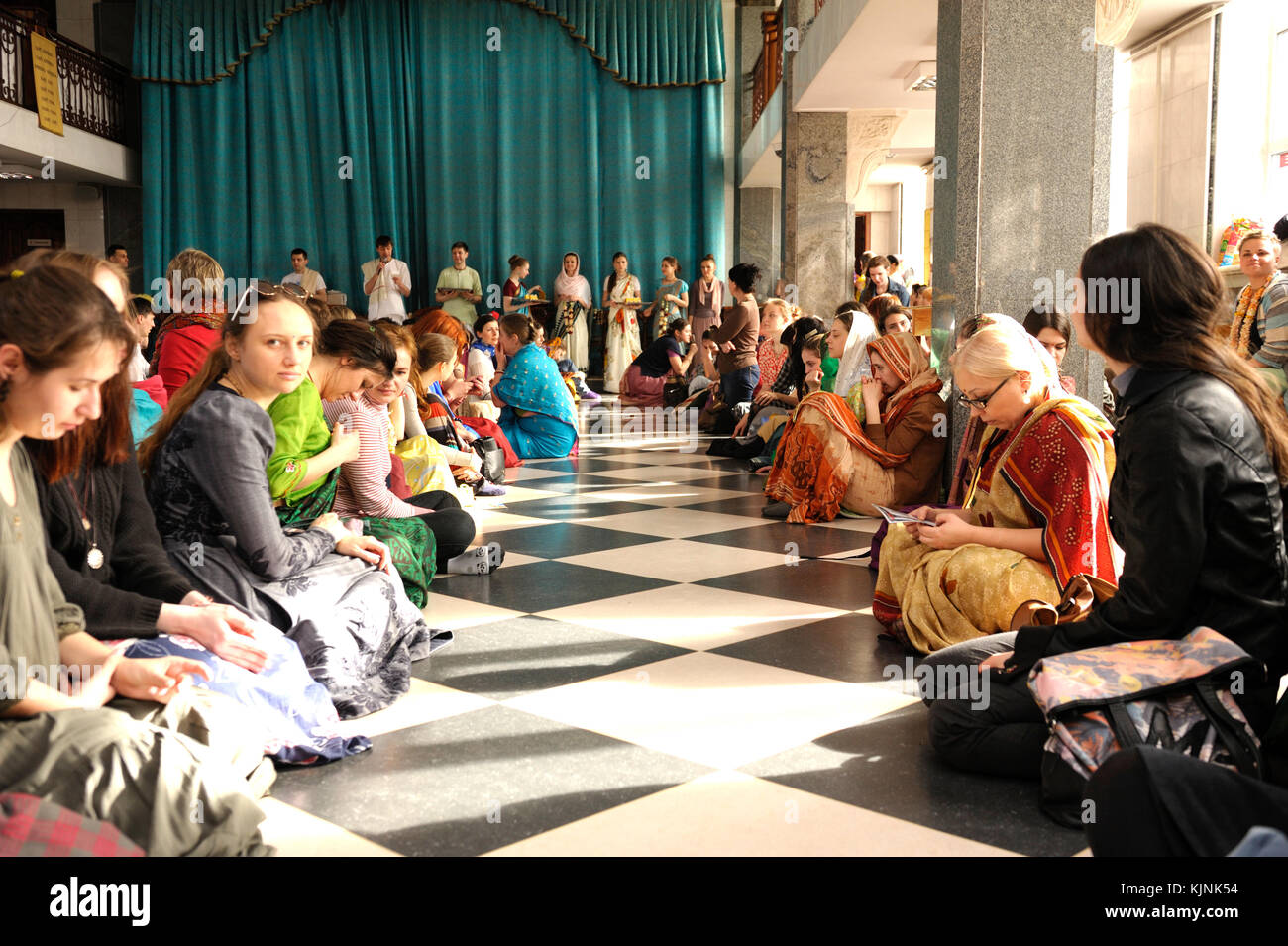 Krishna parishioners sitting on a floor in a temple and waiting for attendants giving them Prasad - food that is Stock Photo