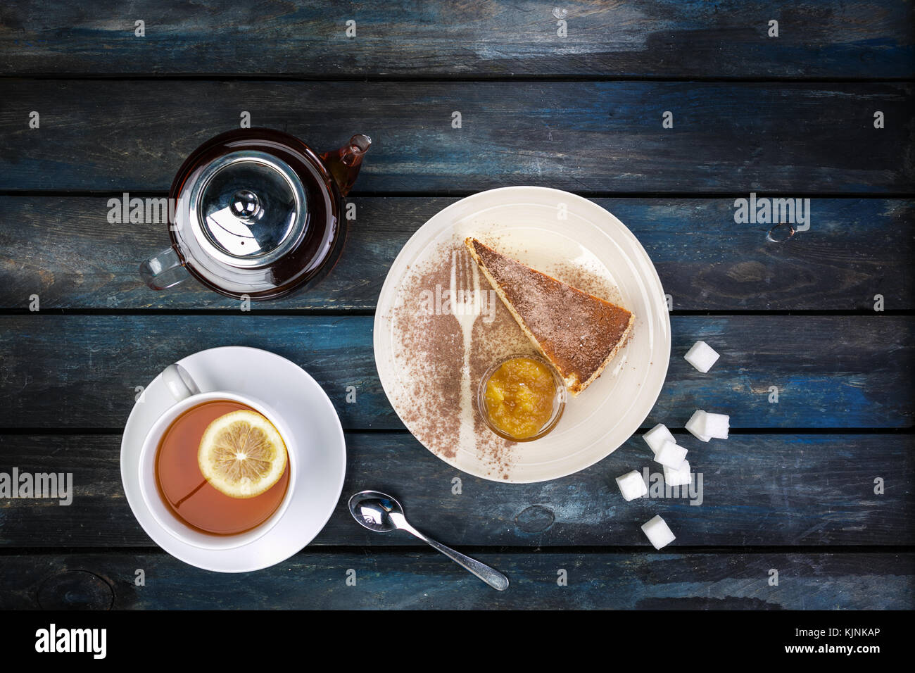 Slice of Cheesecake with jam rafinated sugar and tea kettle with lemon on a colored wooden background. Top view - Stock Image