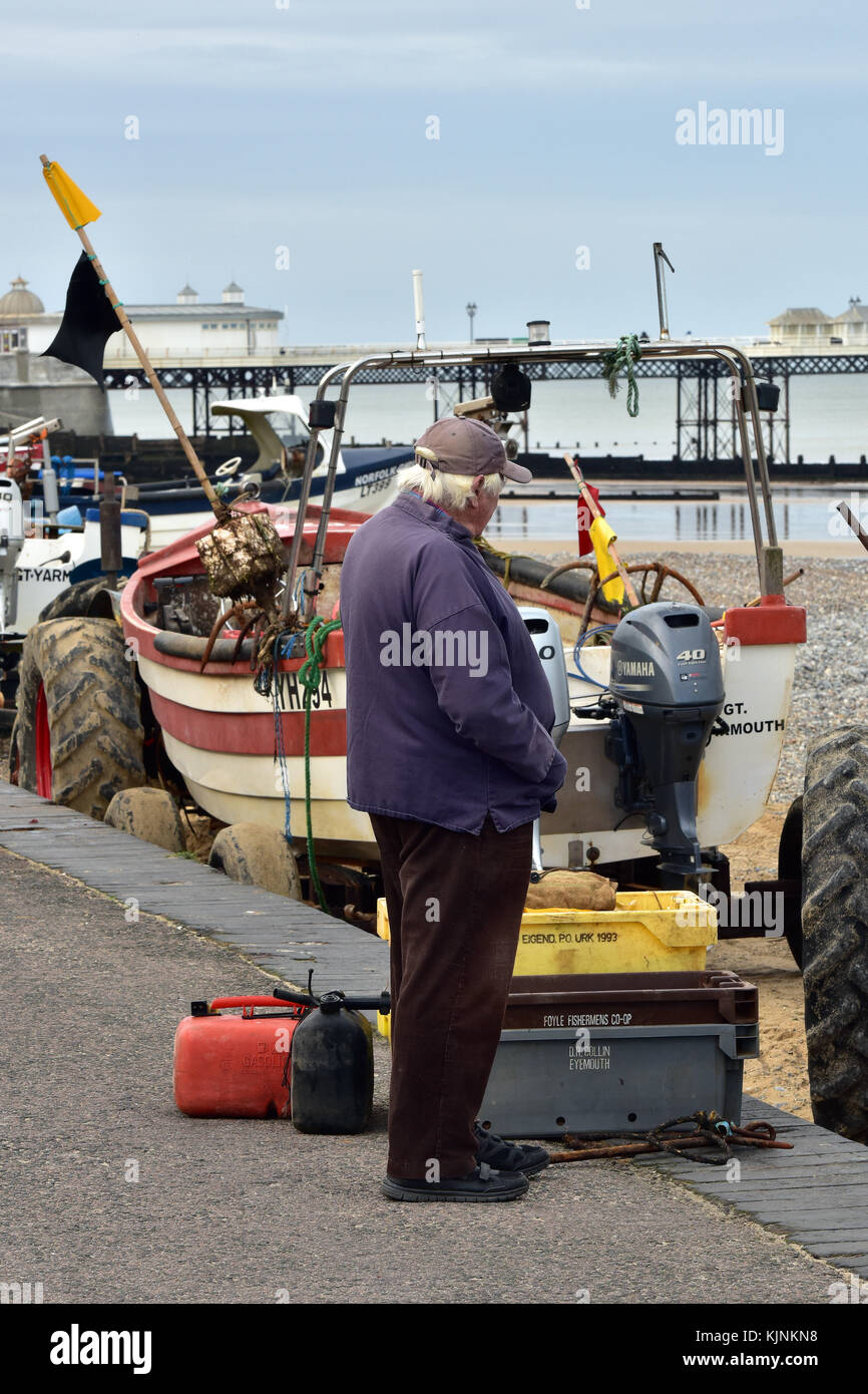 an old fisherman or salty old sea dog standing on the beach at Cromer in Norfolk next to the Victorian pier and - Stock Image