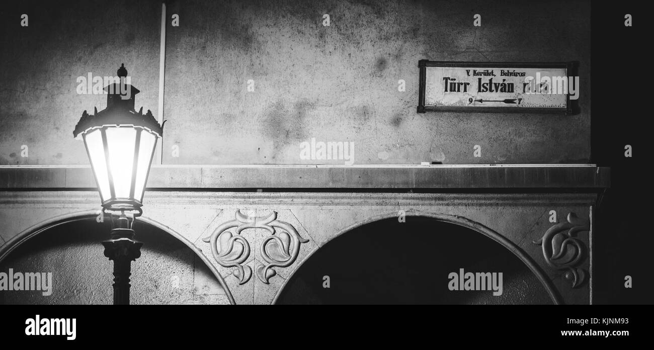 Black and white photo of a street lamp post and a vintage street name sign in