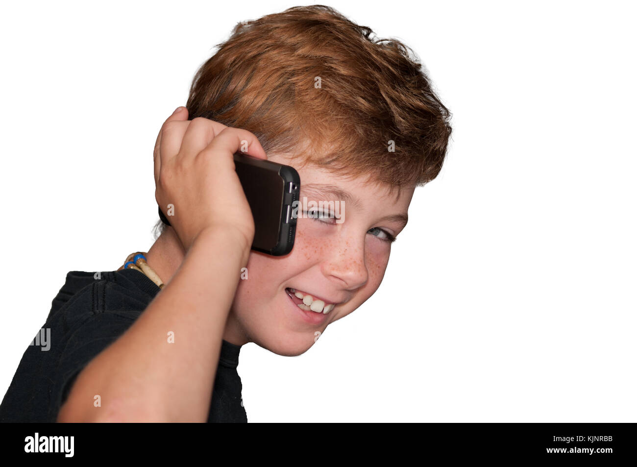 Young pre-teen boy with red hair smiling while talking on a smart cell phone. - Stock Image