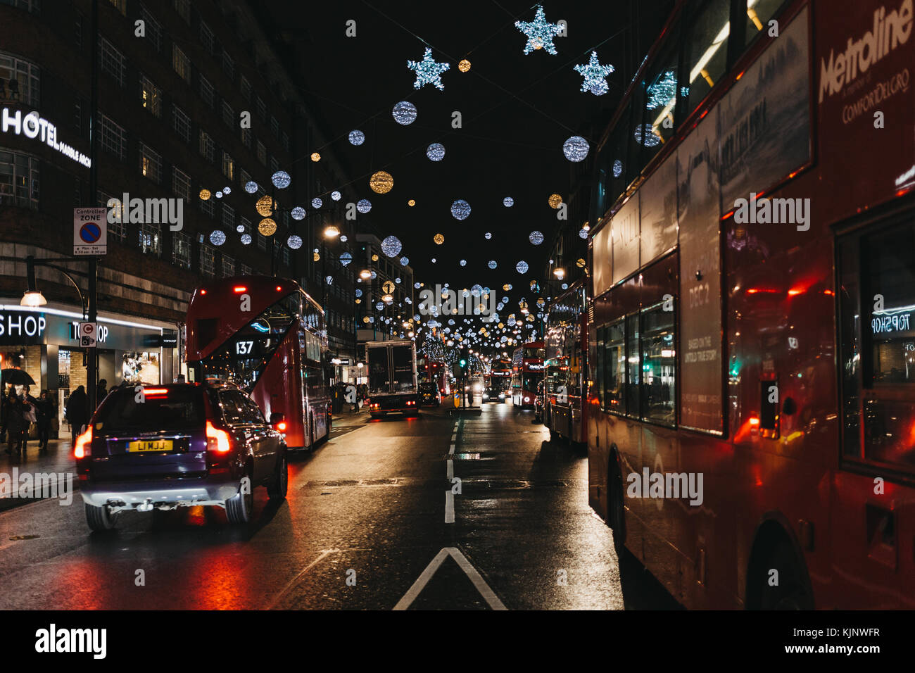 Double Decker red buses, black cabs and cars on Oxford Street decorated with Christmas Lights. Oxford Street if - Stock Image