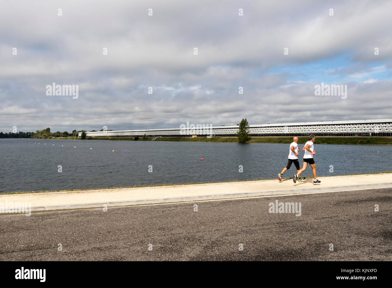 Two runners in the Bordeaux Le Lac, the Lake, and the Bordeaux Exhibtion Centre - Stock Image