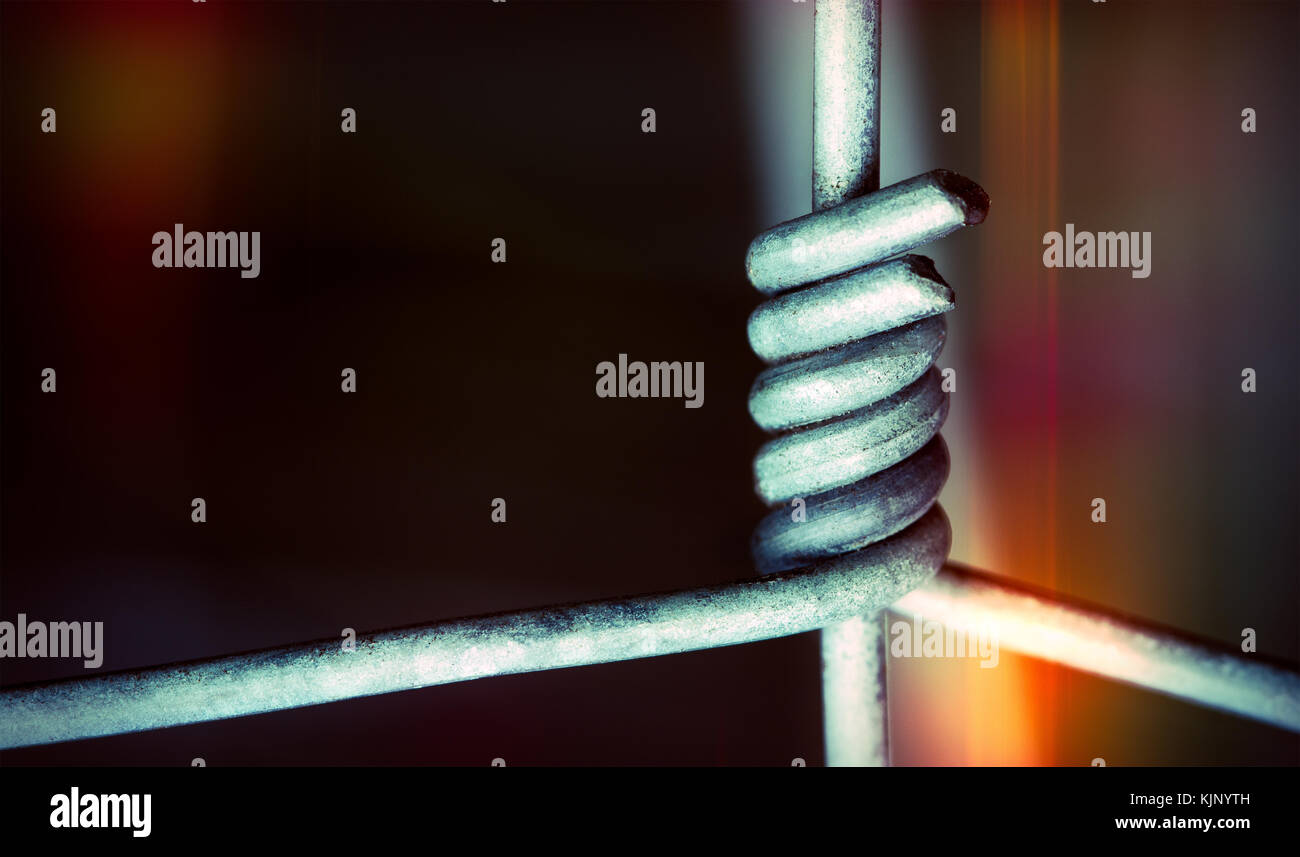 Metal wires in tight connection on dark colored background. Close-up of fence as concept of clasping, cooperation, - Stock Image