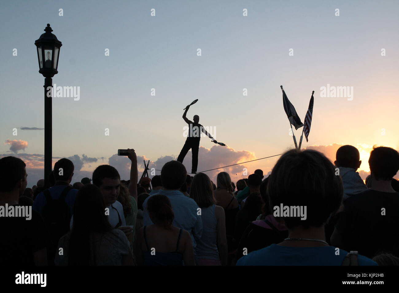 Acrobat  walking on a wire at sunset in Mallory Square, Key West, Florida. - Stock Image