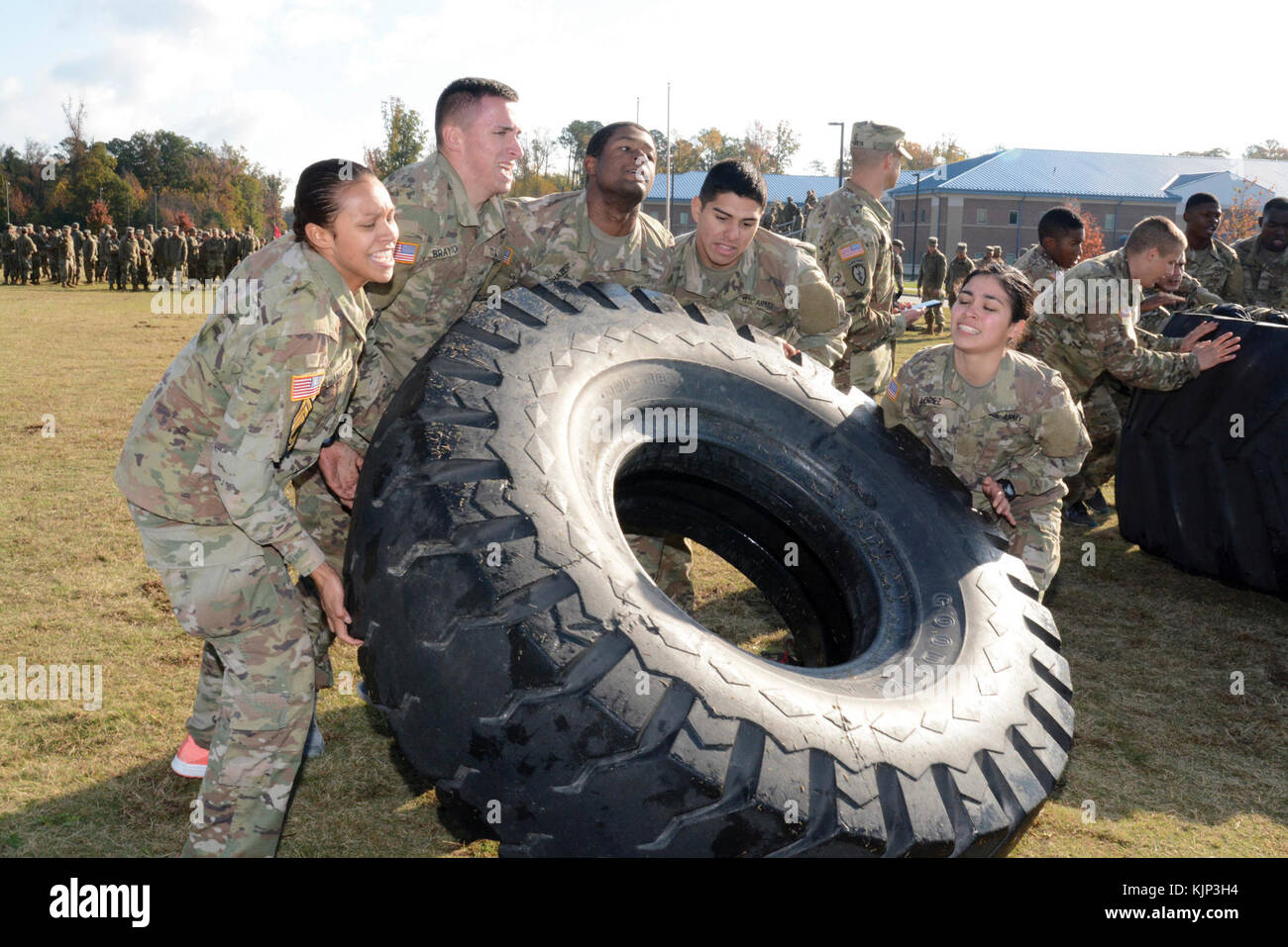 Soldiers from Bravo Company, 16th Ordnance Battalion, tackle a physically demanding tire flip obstacle that was - Stock Image