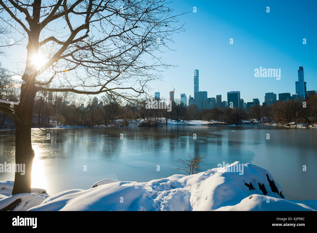 Scenic view of the Manhattan skyline reflecting in the ice of the frozen Central Park lake the morning after a winter Stock Photo