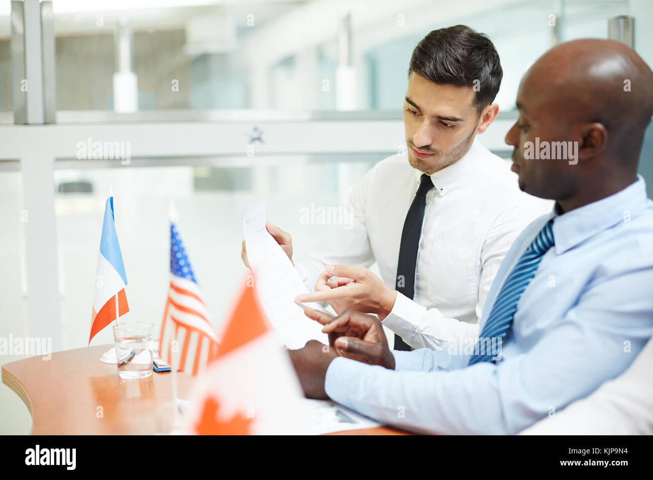 Intercultural politicians discussing terms of international partnership contract after conference - Stock Image