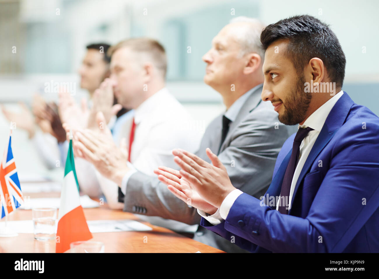 Group of politicians congratulating speaker by ovations after making report at conference - Stock Image