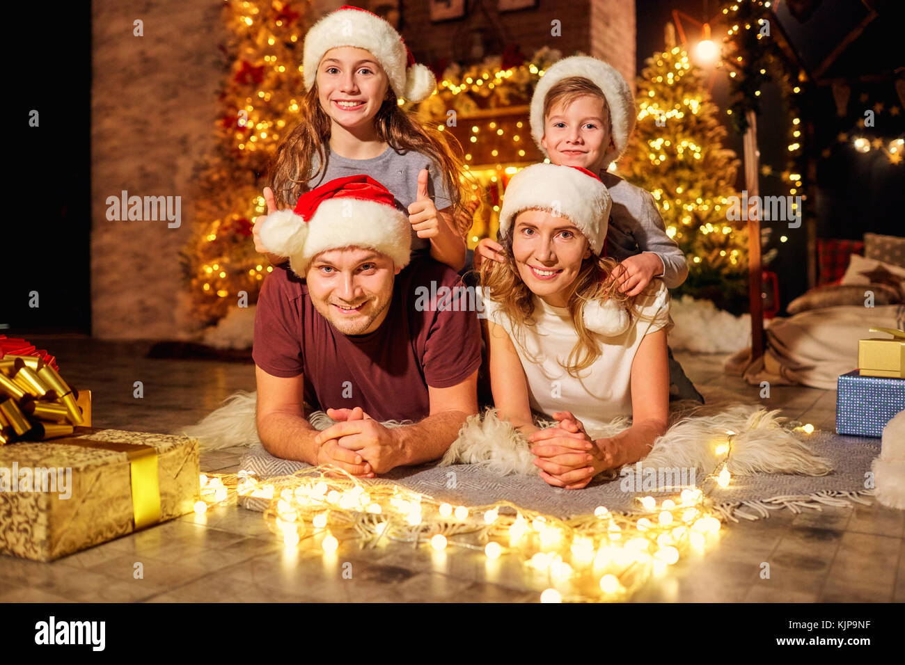 Family in a room with a Christmas tree on Christmas Day. - Stock Image