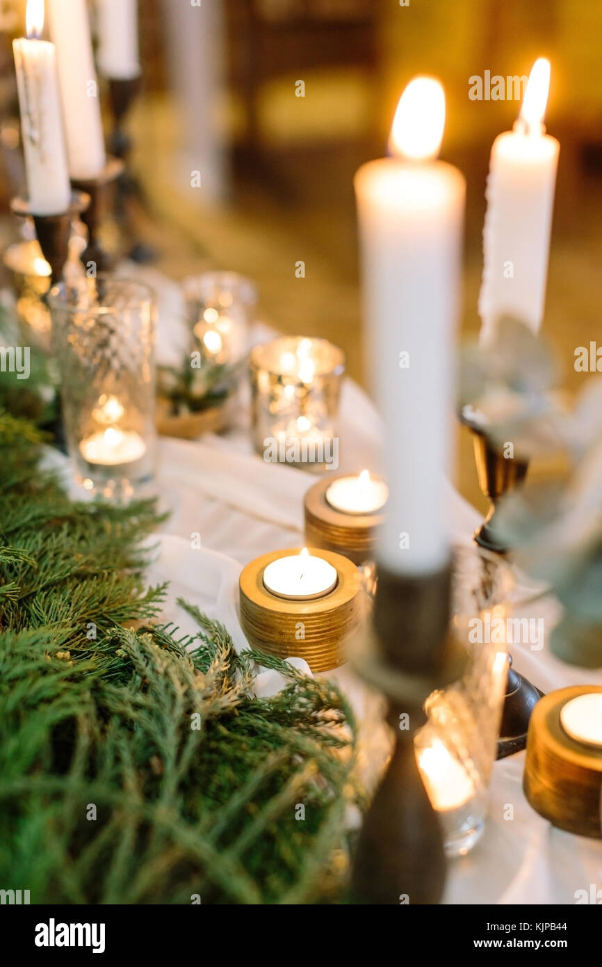 illumination, comfort, christmas feast concept. table with numerous of candles in various holders made of glass, Stock Photo