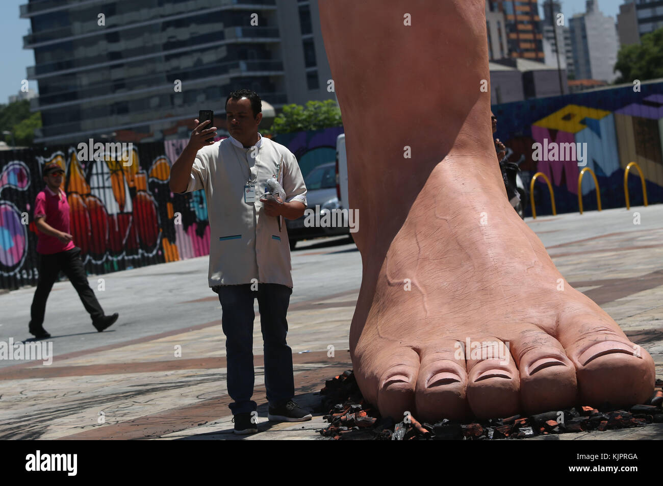 Sao Paulo, Brazil. 29th Nov, 2017. A man stands by a sculpture of a giant foot stepping on hot coals, of Brazilian - Stock Image