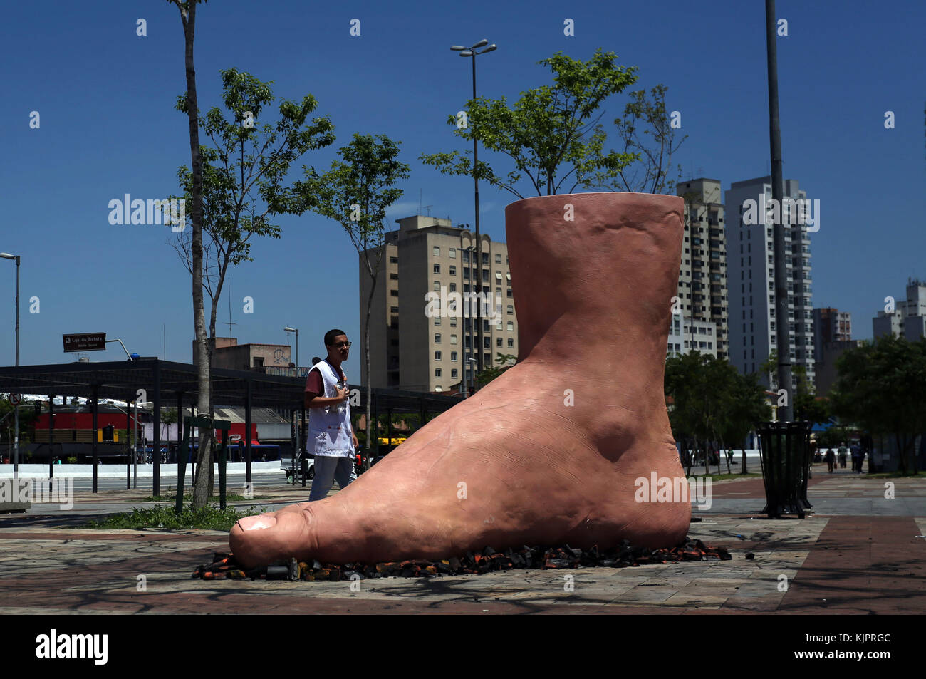 Sao Paulo, Brazil. 29th Nov, 2017. A man watches a sculpture of a giant foot stepping on hot coals, of Brazilian - Stock Image