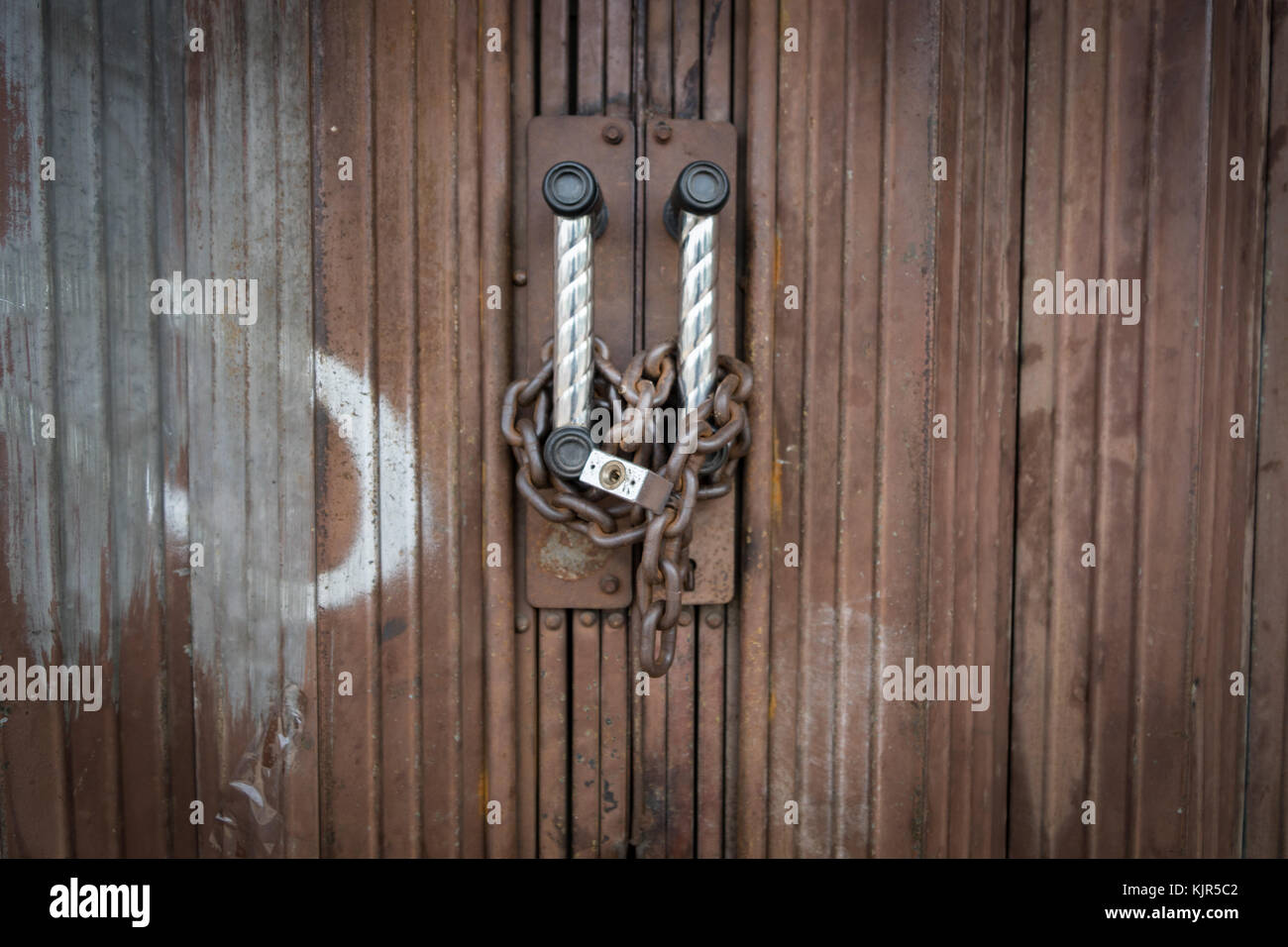 Padlock and chain locked securely on rusty door. - Stock Image